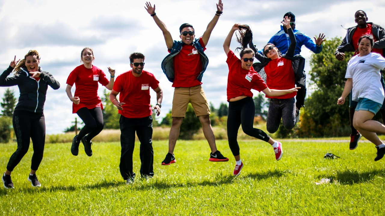 A group of students attending the Student Leadership Academy wearing red tshirts jumping in the air.